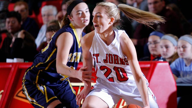 St. Johns' Maddie Maloney, right, drives against DeWitt's Madison Petersen Friday, Dec. 16, 2016, in St. Johns, Mich.