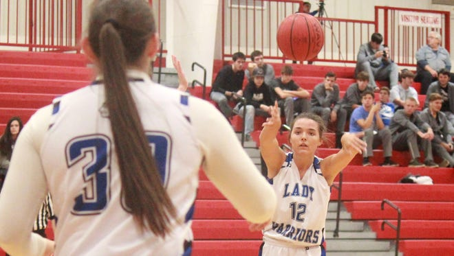 Cotter's Macie Clawson passes to Marie Reed on Saturday in the Arvest Bank Tournament at Flippin.
