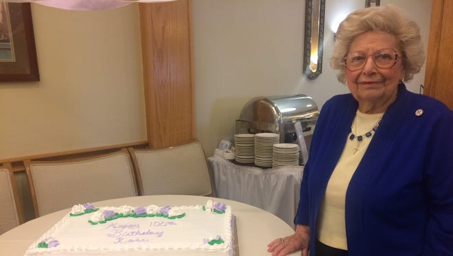 Rose Arbes stands next to one of two cakes served to residents during lunch at the Bellevue Retirement residential facility in Bellevue, Wis., in honor of her 100th birthday Monday, March 20, 2017.
