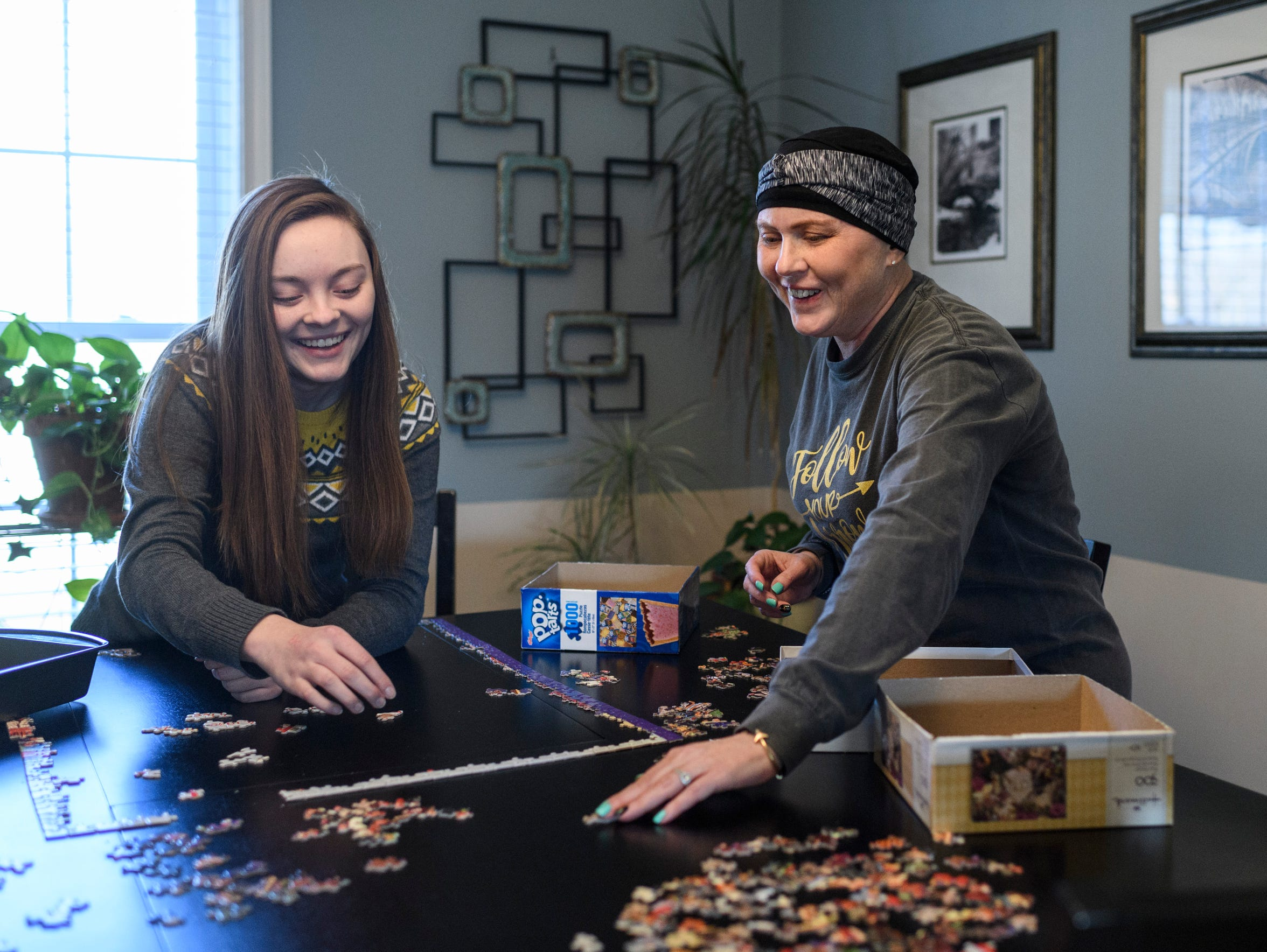Grace and Amy share a laugh as they work on a puzzle