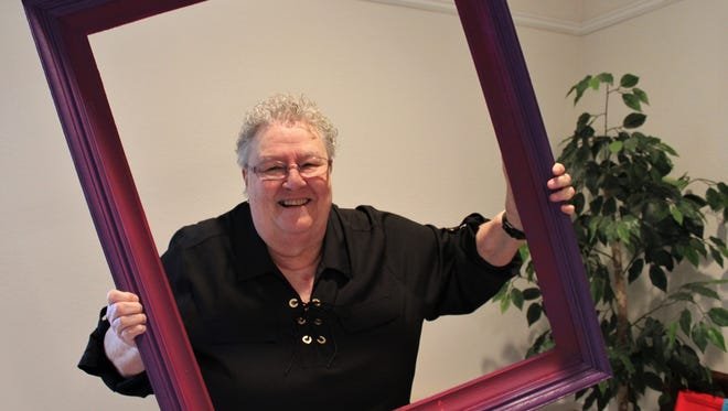 Margaret Warn-Walker, retiring pastor of Metropolitan Exodus Community Church, playfully poses in a purple frame at a retirement reception in her honor at the church June 9.