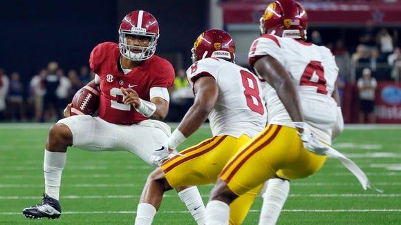 Alabama quarterback Jalen Hurts, left, carries as Southern
