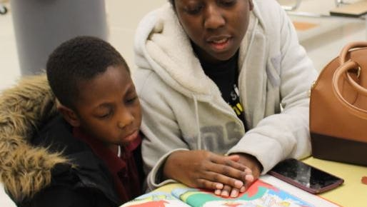 """Anton Winrow listened to his mother Elisha Mitchell read a Dr. Seuss book during """"QML Loves to Read: Read Across America Night"""" at Quarter Mile Lane School in Bridgeton."""
