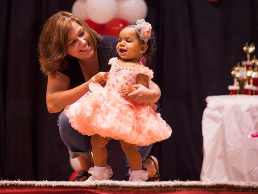 Trisha Bosserman holds onto her daughter, 1-year-old Aveah Henderson, as they walk the stage in front of judges during the Baby Miss division of the Miss Augusta County Fair 2014 Beauty Pageant at Augusta Expoland in Fishersville on Saturday, Aug. 2, 2014.