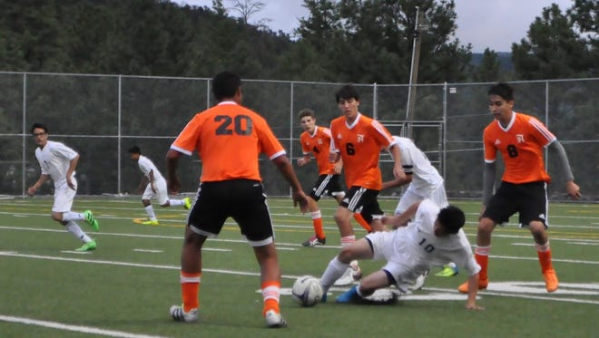 Ruidoso High's Christian Garcia protects the ball from Artesia's Jesus Valdez.