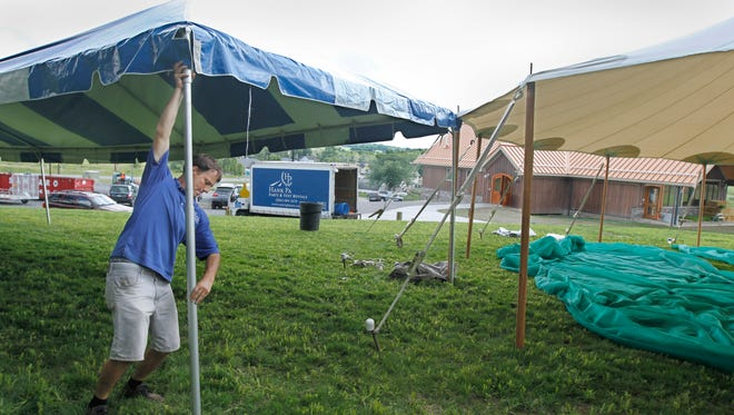 Dave Berardi, vice president, Hank Parker's Party & Tent Rentals of Rochester, puts up one of five large party tents Wednesday during preparations for the upcoming Hopsfest at Nedloh Brewing Co.