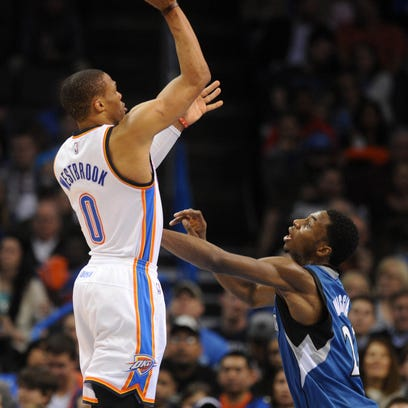 Jan 26, 2015; Oklahoma City, OK, USA;  Oklahoma City Thunder guard Russell Westbrook (0) shoots the ball as Minnesota Timberwolves forward Andrew Wiggins (22) defends during the first quarter at Chesapeake Energy Arena. Mandatory Credit: Mark D. Smith-USA TODAY Sports