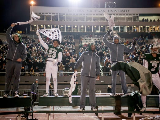 Eastern Michigan Eagles players on the bench cheer