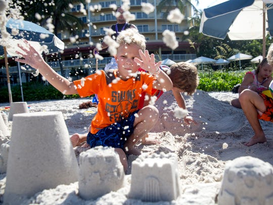 Cole Stroup, 6, throws sand during the Golisano Children's