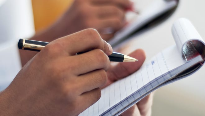 Business people writing on notepad