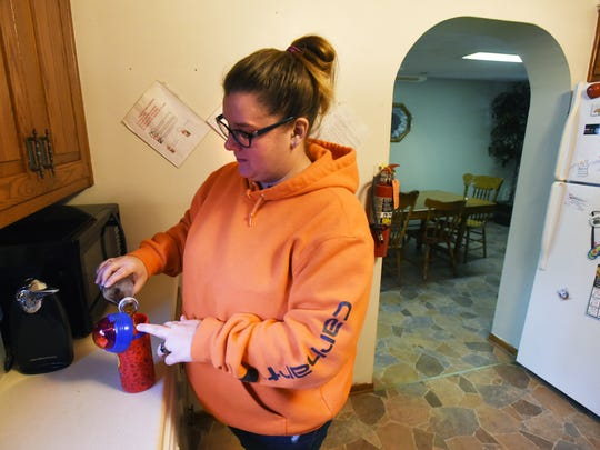 Melanie Snyder gets a drink for a resident at a residential home for people with developmental disabilities in Coshocton.