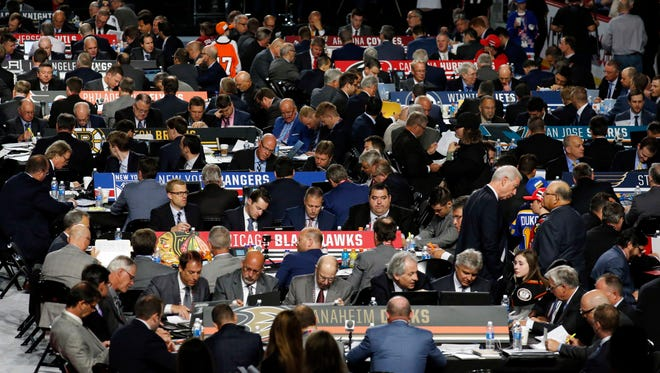 Representatives from NHL hockey teams begin their work during the third round of the NHL hockey draft, Saturday, June 24, 2017, in Chicago.
