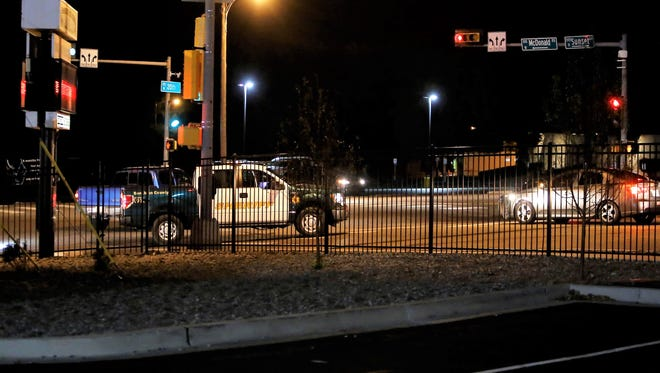 A San Juan County sheriff's vehicle helps escort drivers out of the Farmington High School parking lot at East 20th Street and Sunset Avenue following Friday's Piedra Vista-Highland football game amid a search for a shooting suspect.
