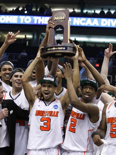 U of L's Peyton Siva, #3, center, and Russ Smith, #2, hoist the regional trophy as they gain a trip to the Final Four with their win over Florida during their NCAA tournament game in Phoenix, Az.