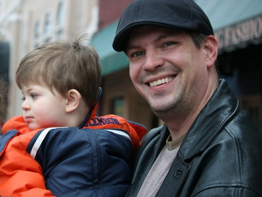 Alec Saidat holds his son Kol on Sunday during the Anderson Christmas Parade.