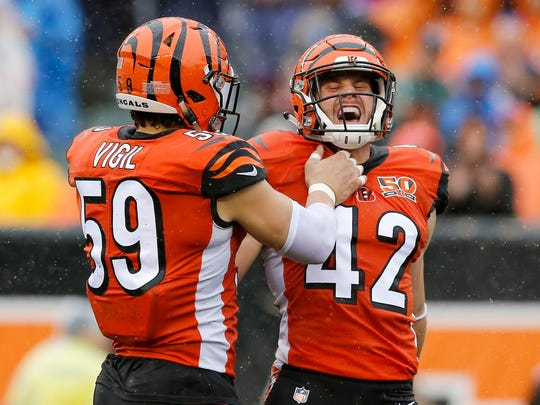 Cincinnati Bengals outside linebacker Nick Vigil (59) and strong safety Clayton Fejedelem (42) celebrate a stop in the first quarter of the NFL Week 5 game between the Cincinnati Bengals and the Buffalo Bills at Paul Brown Stadium in downtown Cincinnati on Sunday, Oct. 8, 2017.