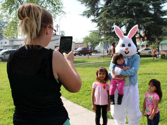 A mother snaps a photo of her children with the Easter
