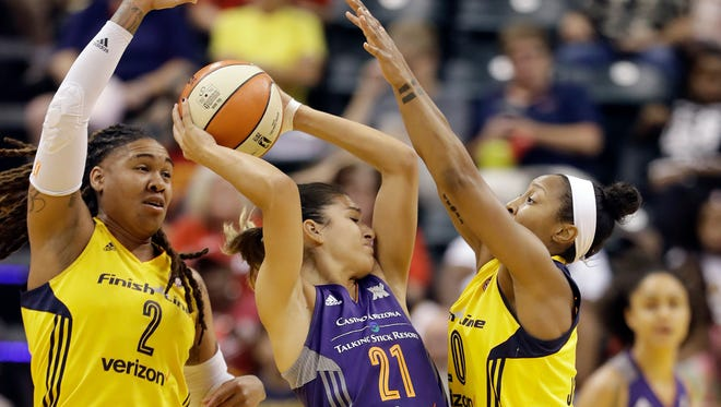 Phoenix Mercury's Marta Xargay (21) is defended by Indiana Fever's Erlana Larkins (2) and Briann January (20) during the first half of their first round WNBA playoff game on Sept. 21, 2016, in Indianapolis.