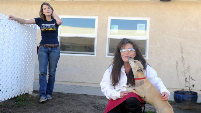 Rachelle Solis, animal behaviorist with nonprofit, Pivot gets a kiss from Nino. In the background is Kimberly Flavin, animal behaviorist, with county of Ventura. Pivot aims to save shelter dogs while providing Juvenile Hall and county jails inmates with career paths for working and training animals.