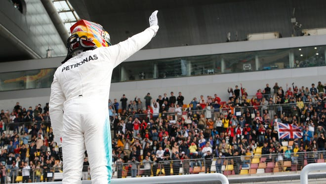 Mercedes driver Lewis Hamilton of Britain waves to spectators after taking pole position for the Chinese Grand Prix.