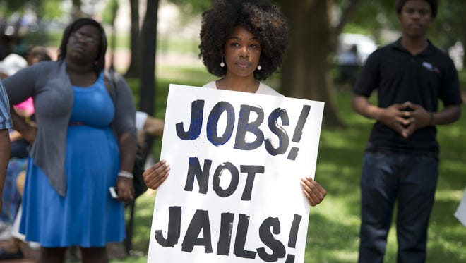 "A demonstrator holds a sign during a rally following a protest march to end the so-called ""war on drugs,"" which they say leads to mass incarceration of African Americans."