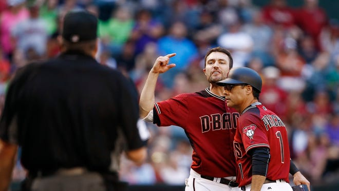 Arizona Diamondbacks' A.J. Pollock, center, is held back by third base coach Tony Perezchica, right, as he argues with umpire Jerry Layne, left, after Pollock was ruled out at second base during the 10th inning of a baseball game Sunday, April 30, 2017, in Phoenix.