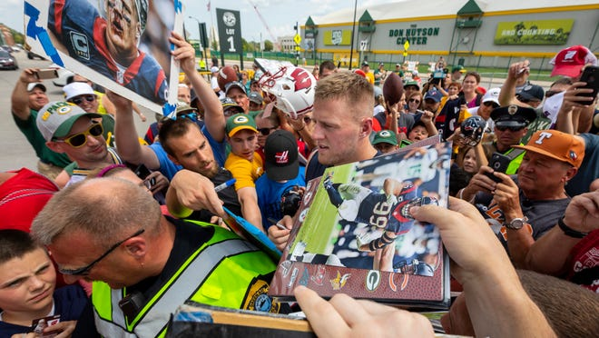 The Texans' J.J. Watt signs autographs after a joint practice with the Packers on Monday in Green Bay.