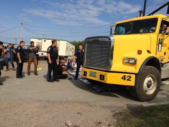 Williston police officers help a truck driver maneuver past Rising Tide Vermont protesters at Vermont Gas in Williston on Wednesday morning.