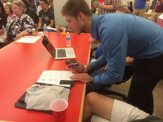 An attendee at the charity hackathon makes a list of potential projects he can help with.  Nine charities pitched projects for the more than 80 people in attendance.
