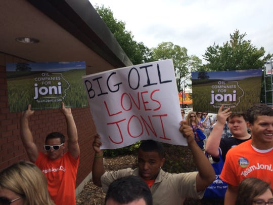 Opponents of Joni Ernst's senate candidacy appeared with handmade and professional signs linking her to oil companies.