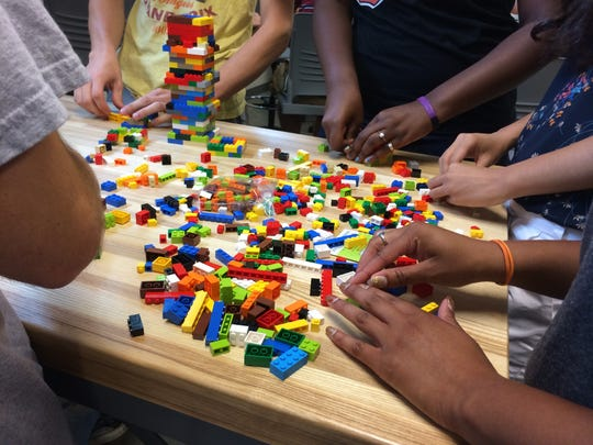 Students in Purdue University's College of Technology used LEGOS to build towers that could hold a two-liter bottle for 10 seconds as part of the new competency-based degree program.