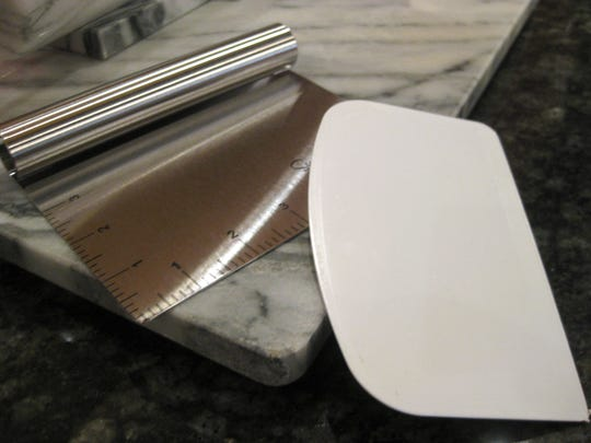 A plastic bowl scraper (right) can get the last bit of cookie dough out of the mixing bowl with ease. This metal dough cutter (left)  has handy inch markings. (Sur La Table.)