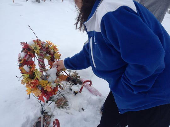 Denise Owens places a wreath on the grave site of Amber and Kevin Stitt in Edinburgh.