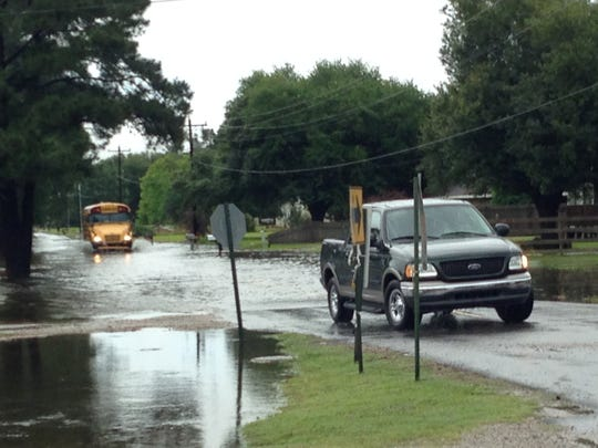 Vehicles try to navigate a flooded Cankton Road in Carencro.
