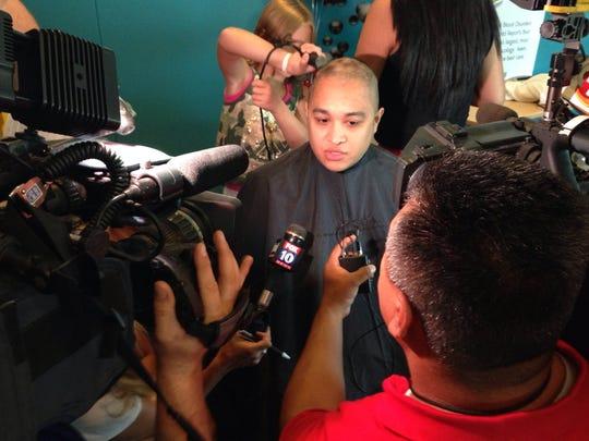 Patrick Tomboc speaks to the media while Elizabeth Blair shaves his head.