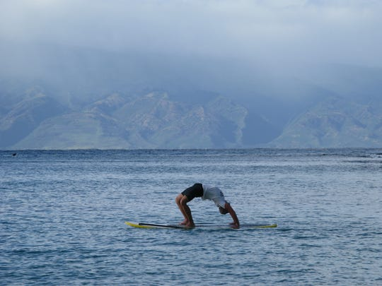 Stand-up paddleboard instructor Corby Hettler can do it all - even yoga - on his board in  Napili Bay.