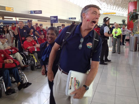 Central Valley Honor Flight organizer Al Perry swoons after getting a kiss from Otelia El'Amin after arriving at Baltimore Washington Airport, on Monday. It was Day One of a three-day trip to Washington, D.C., for nine Tulare County veterans of World War II.
