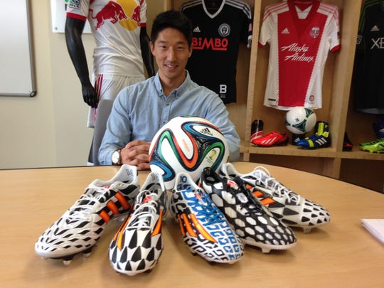 Peter Hong, merchandise manager for adidas, poses with the company's Battle Pack collection of soccer boots and the Brazuca, the official ball of the 2014 World Cup, at the conpany's headquarters in Portland, Ore. (AP Photo/Anne Peterson)