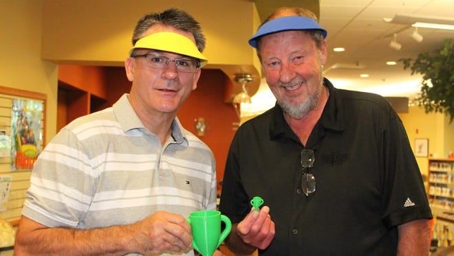 Baxter Bulletin managing editor Bob Heist (left) holds the champion's trophy after playing a benefit putt-putt challenge with KTLO general manager Bob Knight (right) as part of the second annual Mini Golf FUNdraiser at Donald W. Reynolds Library.