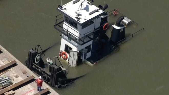 A tugboat sinks after being entagled in rigging and taking on water at a construction barge near the Tappan Zee Bridge Thursday, June 30, 2016.