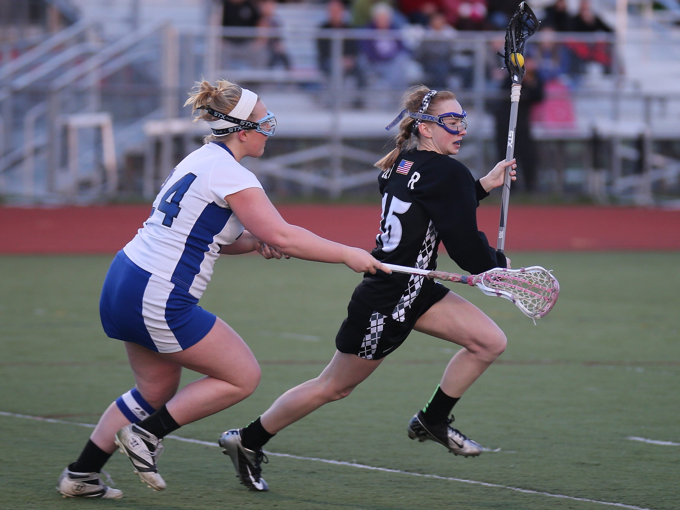 Plymouth's Cathryn VandenBosch (No. 15) tries to escape the defensive pressure of Salem's Megan Finkbeiner (No. 44) during Wednesday night's varsity girls lacrosse match.