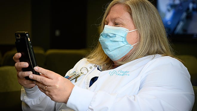 Flagler Health+ manager of infection prevention Kerry Spann-Caride demonstrates a smartphone-based program developed to track employee health at Flagler Hospital in St. Augustine on Friday.
