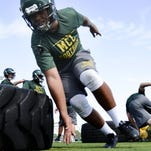 Football players at Melbourne Central Catholic work on their technique during practice Tuesday afternoon.