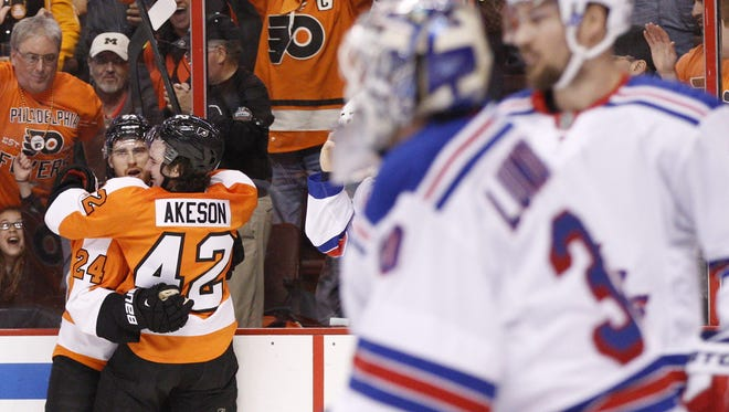 The Flyers' Matt Read, left, celebrates his goal against  Rangers goalie Henrik Lundqvist, front  right,  with Jason Akeson  during the first period of Game 4  Friday night.