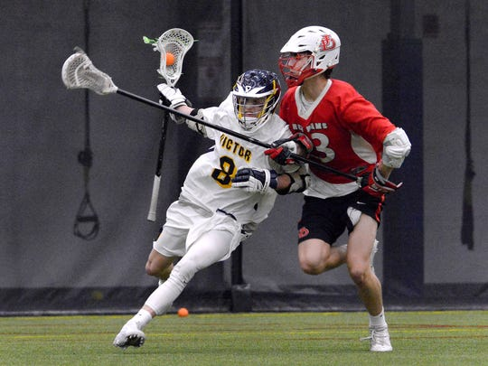 Victor's Sam Lambert, left, is defended by Jamesville-Dewitt's Matthew Bradford during the season opener played at the Pinnacle Athletic Campus, Thursday, March 29, 2018.