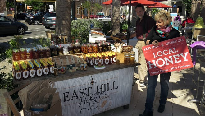 Ellen Kawamura of the East Hill Honey Co. puts out a sign advertising her company at the Market at Al Fresco on Wednesday afternoon.   photos by Bruce Graner/bgraner@pnj.com Ellen Kawamura of the East Hill Honey Co. puts out a sign advertising the presence of her company at the Al Fresco Market Wednesday afternoon.