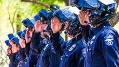 Phoenix police officers salute as the casket of Phoenix