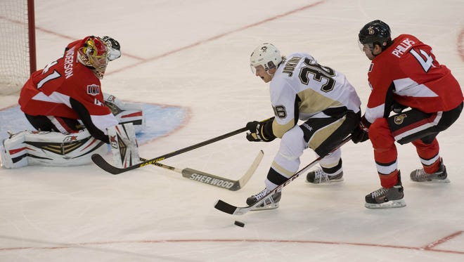 Ottawa Senators goalie Craig Anderson takes the puck away from Pittsburgh Penguins left wing Jussi Jokinen in the third period at the Canadian Tire Centre.
