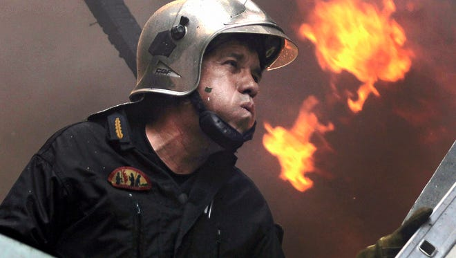 A fireman tries to extinguish a fire in the Karea suburb of Athens. Due to the strong winds blowing in the area the blaze is now very close to the inhabited areas.