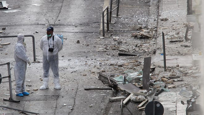 Police experts search for evidence outside the Hellenic Federation of Enterprises (SEV) following a bomb explosion in central Athens, Greece, 24 November 2015.